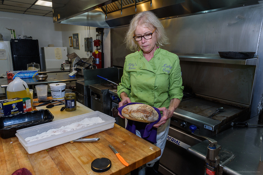 Chef Cary carries a boule from the oven. Lunchtime in the kitchen at Lilly's Monday, Aug. 15, 2016 with Chef/Owner Kathy Cary and staff. (Photo by Brian Bohannon)