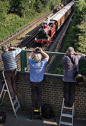 © Licensed to London News Pictures. 22/06/2019. London, UK. People watch from a bridge as a Metropolitan Locomotive No 1 steam engine pulls a set of vintage coaches as it approaches Ealing Brodaway Undergound station to celebrate the 150th anniversary of the district line. London Transport Museum is running steam services, with vintage coaches, between Ealing Broadway and High Street Kensington over this weekend. Photo credit: Peter Macdiarmid/LNP