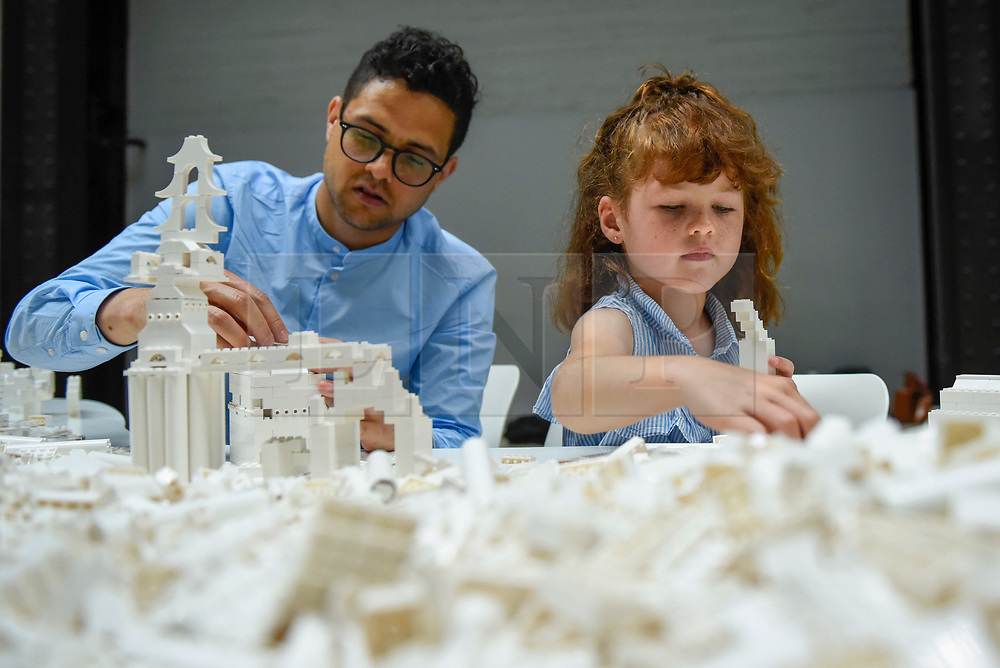 "© Licensed to London News Pictures. 26/07/2019. LONDON, UK. Daisy Lenkiewicz, aged 6, and her father Simon work with Lego at the preview of ""The cubic structural evolution project"", 2004, by Olafur Eliasson at Tate Modern.  Exhibited for the first time in the UK, the artwork comprises one tonne of white Lego bricks inspiring visitors to create their own architectural vision for a future city and is on display until 18 August 2019.  The work coincides with the artist's new retrospective exhibition ""In real life"" at Tate Modern on display to 5 January 2020.  Photo credit: Stephen Chung/LNP"