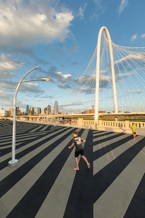Kids playing on Continental Avenue Bridge with Margaret Hunt Hill Bridge in background, Trinity River, Dallas, Texas, USA.