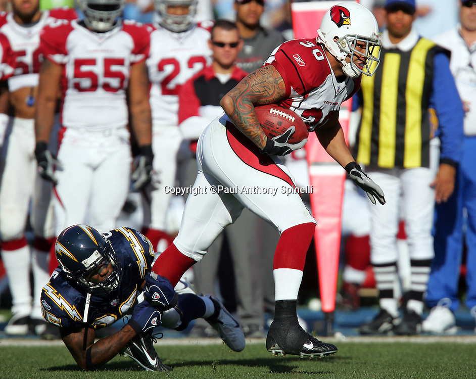 SAN DIEGO - DECEMBER 31:  Fullback Obafemi Ayanbadejo #30 of the Arizona Cardinals pulls away from an ankle tackle by cornerback Antonio Cromartie #25 of the San Diego Chargers at Qualcomm Stadium on December 31, 2006 in San Diego, California. The Chargers defeated the Cardinals 27-20 to secure the number one seed in the AFC playoffs. ©Paul Anthony Spinelli *** Local Caption *** Obafemi Ayanbadejo;Antonio Cromartie