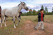"""09 SEPTEMBER 2007 -- ST. MICHAELS, AZ: ISIAH WHITEHORSE, 5, from Many Farms, AZ, walks Joey before his brother, Dominick, rode the horse in a traditional Navajo Horse Race in the summit area of the Navajo Indian reservation about 10 miles west of St. Michaels, AZ. Traditional horse racing is making a comeback on the Navajo reservation. The races are run on improvised courses that vary depending on the local terrain. Use of saddles is optional (except in the """"Cowhand Race"""" which requires a western style saddle) and many jockeys ride bareback. The distances vary from one mile to as long as thirty miles. Traditional horse races were common until the 1950's when they fell out of favor, but there has been a resurgence in traditional racing since the late 1990's and now there is a traditional horse racing circuit on the reservation.  The race was organized by the Begay family of Steamboat, AZ and run on private land about three miles from a paved road.   Photo by Jack Kurtz"""