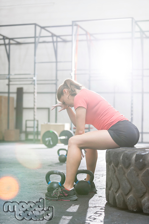 Tired woman sitting on tire in crossfit gym