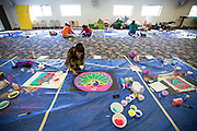 Competitors use colored sand to create pieces of art during the Diwali Rangoli competition at the Shreemaya Krishnadham Temple in Milpitas, California, on November 2, 2013. (Stan Olszewski/SOSKIphoto)
