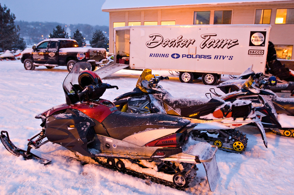 Snowmobiles are parked near the Decker Snow-Venture Tours support vehicle and trailer during a tour of the Keweenaw Peninsula in Michigan's Upper Peninsula.