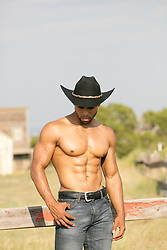 shirtless muscular African American cowboy on a ranch