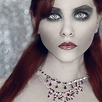 A girl with long red hair in front of a sparkly, silver background wearing a necklace looking at camera