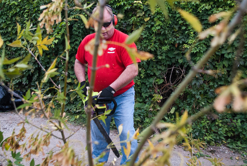 Lathan Goumas | The Bay City Times..Third ward commissioner Dennis Banaszak cuts a tree into smaller pieces using a chainsaw during a neighborhood cleanup around Birney Park in Bay City, MI., on Friday September 23, 2011.