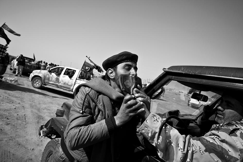 Des combattants rebelles célèbrent leur victoire sur l'armée loyaliste en embrassant le Coran, le 26 mars 2011 après avoir pris la ville d'Aj Dabiya la nuit précédente.