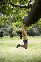 Girl (7-9) hanging from tree