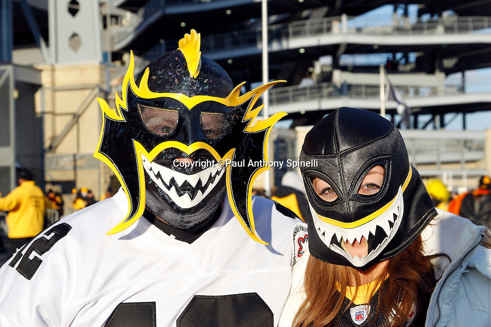 Pittsburgh Steelers fans with face masks pose for a photo before the NFL 2011 AFC Championship playoff football game against the New York Jets on Sunday, January 23, 2011 in Pittsburgh, Pennsylvania. The Steelers won the game 24-19. (©Paul Anthony Spinelli)