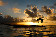 Child doing a backflip from a canoe at sunset. Rah Lava Island, Torba Province, Vanuatu