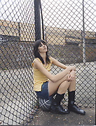 Young woman sitting on basketball leaning head against chain link fence.