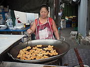 23 JUNE 2015 - BANGKOK, THAILAND: A vendor making Chinese doughnuts, called Pa Thong Ko, in the market in the Wong Wian Yai train station in the Thonburi section of Bangkok.    PHOTO BY JACK KURTZ