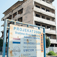 MOSTAR, BOSNIA AND HERZEGOVINA - JUNE 28:  A sign showing a reconstruction project is seen in front of a derelict building damaged by bulletts from the 1993 war is seen on June 28, 2013 in Mostar, Bosnia and Herzegovina. The Siege of Mostar reached its peak and more cruent time during 1993. Initially, it involved the Croatian Defence Council (HVO) and the 4th Corps of the ARBiH fighting against the Yugoslav People's Army (JNA) later Croats and Muslim Bosnian began to fight amongst each other, it ended with Bosnia and Herzegovina declaring independence from Yugoslavia.  (Photo by Marco Secchi/Getty Images)
