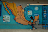 TENOSIQUE, MEXICO - MAY 29, 2014:  Merlit Melissa Nuñez Rodriguez, 6, from Olancho, Honduras who is migrating north fleeing gang violence with her mother and father, looks at a mural of a map of popular migrant routes through Mexico, painted on a wall at the 72 migrant shelter in Tenosique, where  Catholic priests and other volunteers provide mats for migrants to sleep on, second-hand clothes, meals, basic medical treatment, and help applying for immigration visas and refugee status to people traveling north. The shelter, which traditionally has been visited by men between the ages of 15-35, has recently been overrun by women and children in recent months, more than double the amount -- consequential of a recent boom of minors headed to the United States from Central America. PHOTO: Meridith Kohut for The New York Times