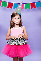8 year old girl wearing pink tutu and clown hat standing on a lavender seamless<br /> Photographed at Photoville Photo Booth September 20, 2015