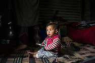 Zainab, 10 months, sits on the floor as her family goes about their daily lives in their temporary shelter in Narbal village, Jammu and Kashmir, India, on 24th March 2015. When the floods hit in the middle of the night, Shugufta and her family had to walk 5 miles to find shelter. Save the Children supported the family with shelter kits, blankets, hygiene items, food and tarpaulin, which they have used to build a temporary shelter next to their crumbled home. Photo by Suzanne Lee for Save the Children