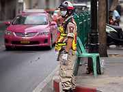 "14 JANUARY 2019 - BANGKOK, THAILAND:       A security guard wearing a dust filter directs traffic on Rama I Road in Bangkok. Bangkok has been blanketed by heavily polluted air for almost a week. Monday morning, the AQI (Air Quality Index) for Bangkok  was 182, worse than New Delhi, Jakarta, or Beijing. The Saphan Kwai neighborhood of Bangkok recorded an AQI of 370 and the Lat Yao neighborhood recorded an AQI of 403. An AQI above 50 is considered unsafe. Public health officials have warned people to avoid ""unnecessary"" outdoor activities and wear breathing masks to filter out the dust.     PHOTO BY JACK KURTZ"