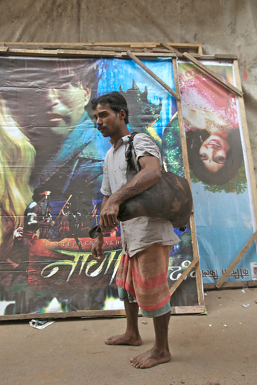Movie posters behind a water man carries water in a goat skin, Kolkata, January 2007