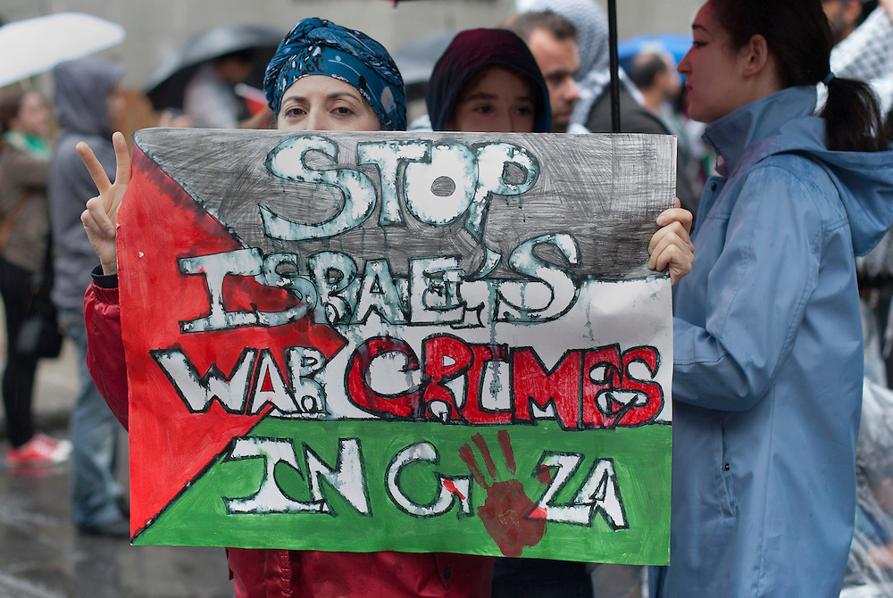 During the march, protesters carry a sign depicting a Palestinian flag with an inscription denouncing war crimes in Gaza.