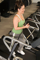 Woman Jogging on Treadmill at Health Club