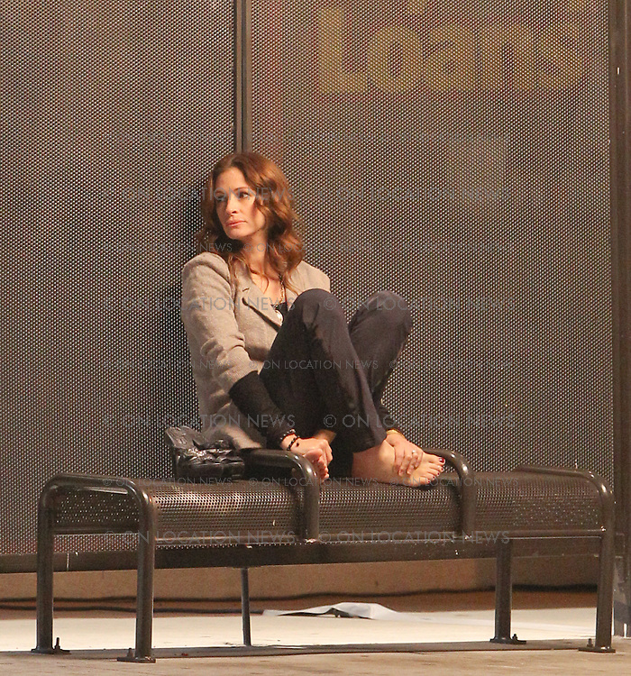 May 28th 2010 Los Angeles, CA. Non Exclusive. Julia Roberts sitting at a bus stop with her shoes off while filming a scene for Larry Crowne. Photo by Eric Ford 818-613-3955 info@onlocationnews.com