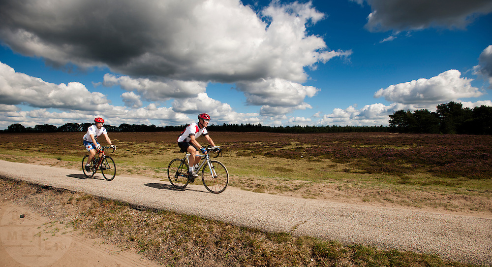 Twee wielrenners rijden op hun racefiets over de Ginkelseheide bij Ede.<br /> <br /> Two cyclist on their racing bikes at the Ginkelseheide nearby Ede.