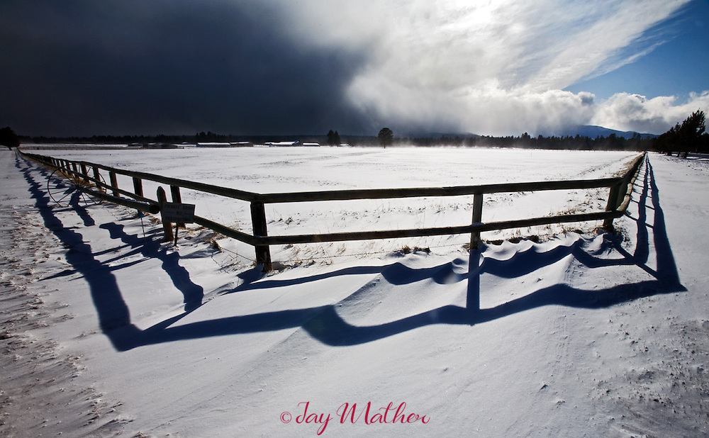 A fence in stark contrast to a snow-filled meadow and a fast moving storm front over the Cascades.