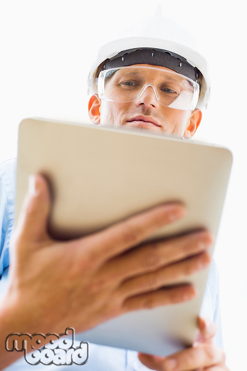 Low angle view of male architect using tablet PC against sky