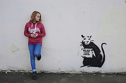 """© Licensed to London News Pictures. 31/10/2015. Folkestone, UK. HOPE WALTERS  age 13  stands next to a new artwork by the artist BANKSY, next to the location of a BANKSY piece that was removed. The Artwork pokes fun at the removal of the last piece which was called """"Art Buff"""", which was of an old lady, and says """"IF FOUND PLEASE CONTACT ALASTAIR. Alastair Upton is the Chief Executive of the Creative Foundation who as called for the picture to be returned to the town. Photo credit:Grant Falvey/LNP"""