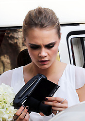 Cara Delevingne  takes pictures with a polaroid camera as she leaves  her  sister Poppy's wedding at St.Paul's Church in Knightsbridge, London , Friday, 16th May 2014. Picture by Stephen Lock / i-Images