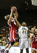 19 February 2009: Wisconsin center Tara Steinbauer (4) pulls down a rebound in front of Iowa guard Kachine Alexander (21) during the first half of an NCAA women's college basketball game Thursday, February 19, 2009, at Carver-Hawkeye Arena in Iowa City, Iowa. Iowa defeated Wisconsin 72-65.