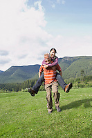 Man carrying woman piggy back in meadow laughing