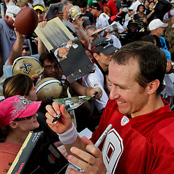 July 28, 2012; Metairie, LA, USA; New Orleans Saints quarterback Drew Brees (9) signs autographs for fans following a training camp practice at the team's practice facility. Mandatory Credit: Derick E. Hingle-US PRESSWIRE