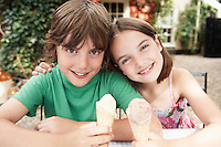 Two Kids Eating Ice Cream Cones at table in back yard portrait