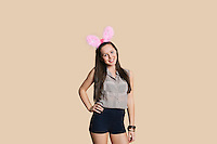 Portrait of a beautiful young woman wearing bunny ears with hands on hips over colored background