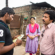 CAPTION: TARU team members educate a slum resident about the benefits of the toll free medi-aid helpline. LOCATION: Bapu Gandhi Nagar, Indore, Madhya Pradesh, India. INDIVIDUAL(S) PHOTOGRAPHED: Anshul Chaturvedi, Megha Burvey (TARU) and unknown.
