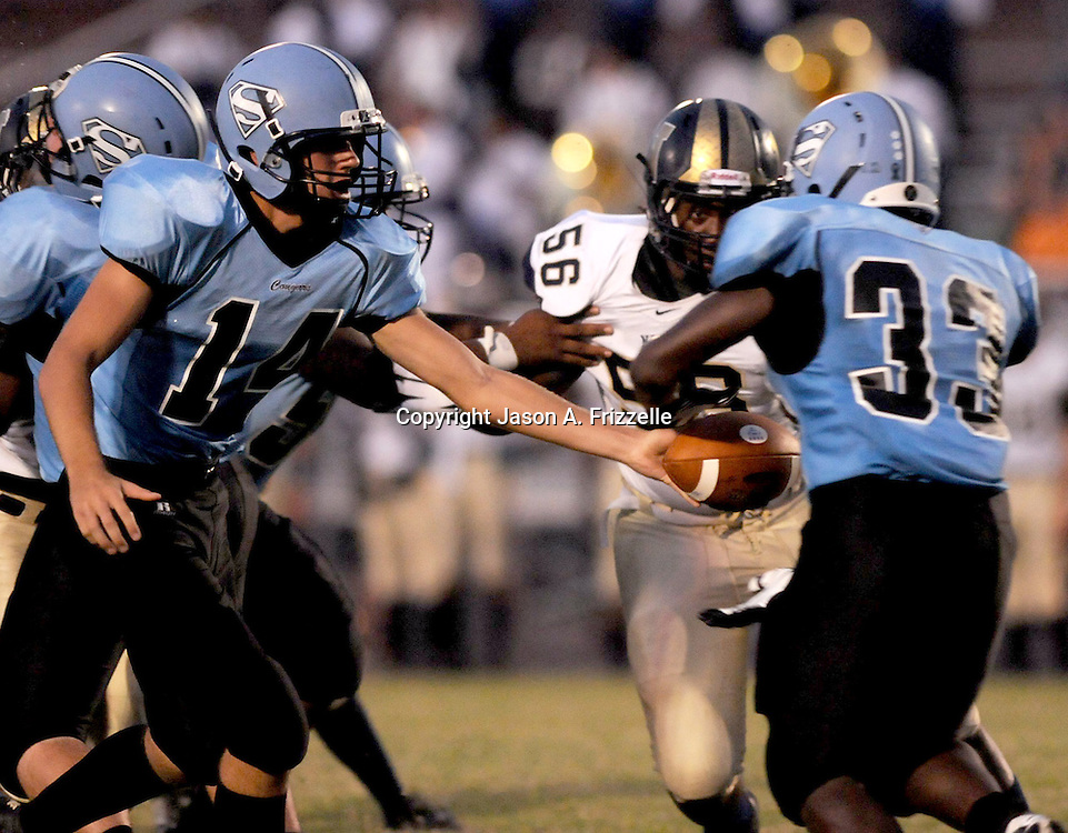 South Brunswick High School's Cole Blackburn hands off to Damani Johnson as North Brunswick's Jabril Robinson looks to tackle Friday September 13, 2013 at South Brunswick High School. (Jason A. Frizzelle)