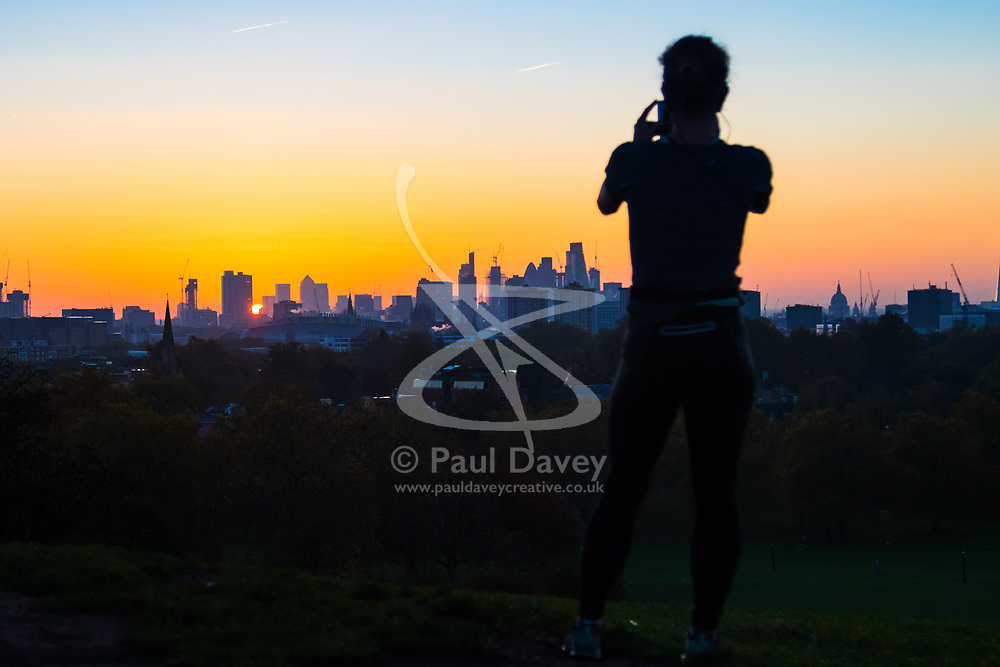 London, October 27 2017. A woman takes a picture was the sun makes its appearance between the skyscrapers of The City as the day breaks over London, seen from Primrose Hill. © Paul Davey