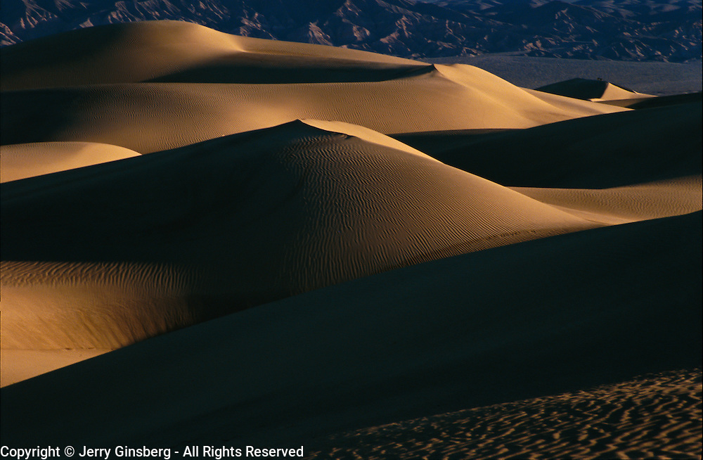 Sultry patterns of light and shadow on Mesquite Flat dunes in Death Valley National Park, CA.