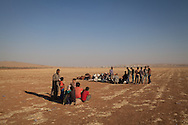 Groups of newly arrived Syrian refugees wait to be collected and taken to temporary shelters around the town of Suruç after crossing the border into Turkey. Their hometown of Kobani in Syria is behind them in the distance.