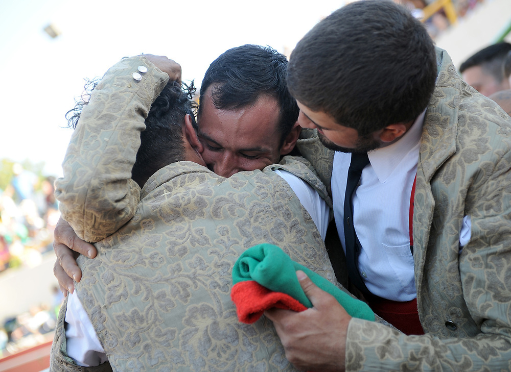 BEA AHBECK/NEWS-SENTINEL<br /> Grupo Forcados Amadores Luso-Americanos' Claudio Pereira is embraced by Donald Mota and Manuel Cabral after his successful grab during the bloodless bullfight during the Our Lady of Fatima Portuguese Festival in Thornton Saturday, Oct. 14, 2017.
