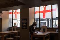 Man in a pub adorned with the St George cross flag representing England. / Un pub avec des drapeaux avec la croix de St George (qui représente l'Angleterre).