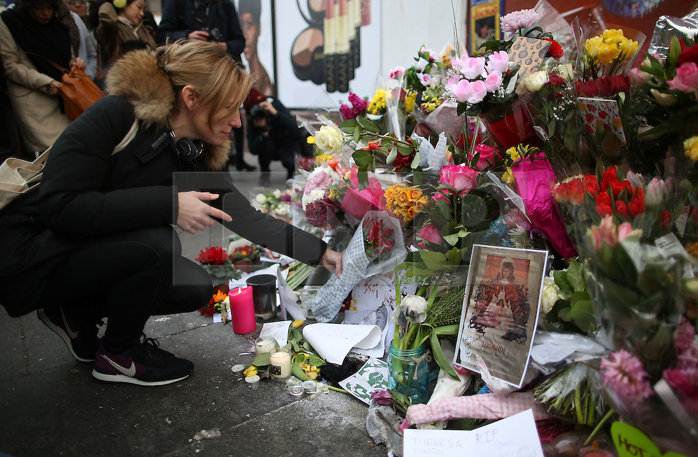 © Licensed to London News Pictures. 12/01/2016. London, UK. Tributes of flowers, cards and candles are placed in front of a mural of David Bowie in Brixton where he was born. Photo credit: Peter Macdiarmid/LNP