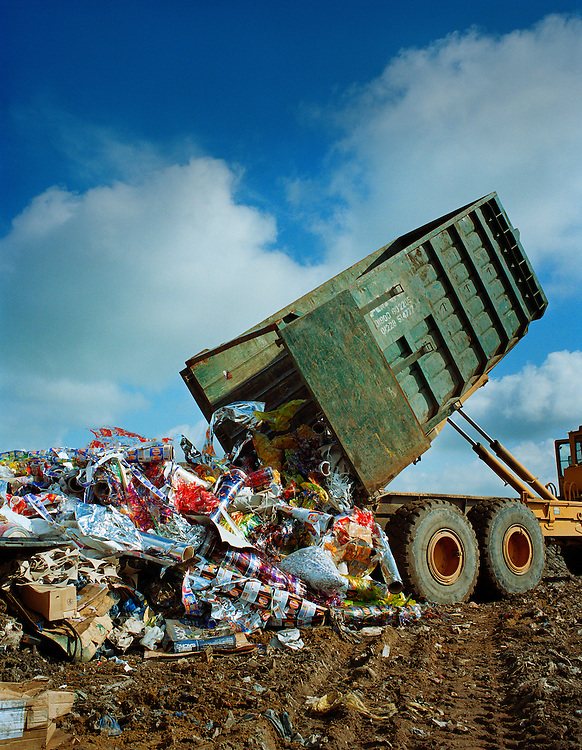 Dumping unused Walkers crisp packaging into a landfill site.