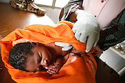Midwife Dagnoko Alima Dambele wraps a newborn child with a piece of cloth at the Badegna community health center in the town of Kita, Mali on Sunday August 29, 2010.
