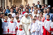 Pope Francis poses with children at the end of his weekly general audience in St Peter's square at the Vatican on April 25, 2018.