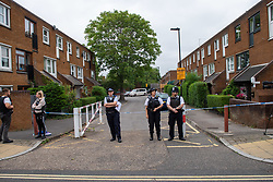 © Licensed to London News Pictures. 04/07/2020. London, UK. Police officers stand at a cordon on Roman Way in Islington. Metropolitan Police Service officers were called at 15:20BST on Saturday, 4 July to Roman Way N7 following reports of shots fired. Officers attended with London Ambulance Service (LAS) and found a man, believed to be aged in his early 20s, suffering from gunshot injuries. Despite their best efforts, he was pronounced dead at the scene. Photo credit: Peter Manning/LNP