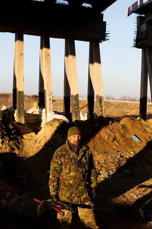 "Volodya, a member of Dnipro-1, poses for a portrait under a fortified bridge about two kilometers from the front on March 9, 2015 near Pisky, Ukraine. The soldiers who defend this position call it ""The Republic of the Bridge."""